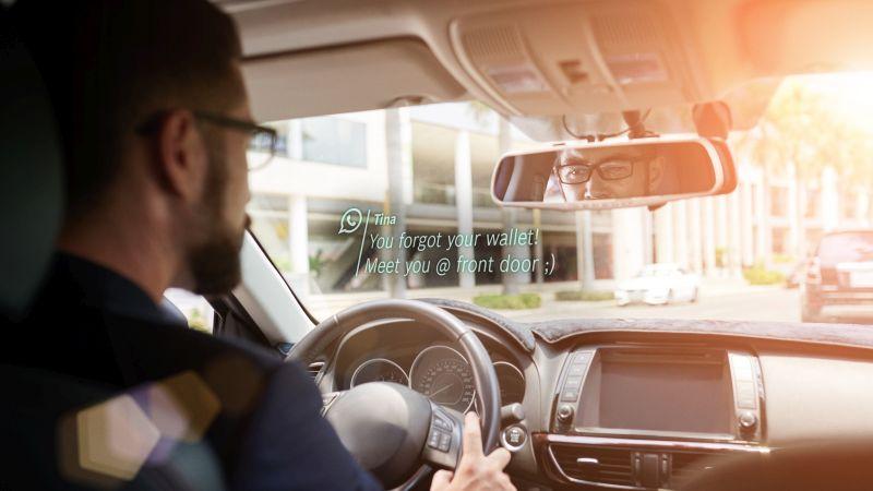 Araba süren kişi gözlüğü bluetooth bağlantısı ile mesajına bakıyor.